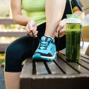 Green detox smoothie cup and woman lacing running shoes before w